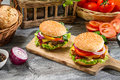 Two homemade burgers made ​​from fresh vegetables on old wooden table Stock Image