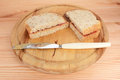Two homemade pb j sandwiches on a wooden board with a sticky knife Royalty Free Stock Photo