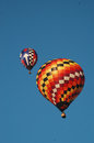 Two hot air ballons race in a clear sky Royalty Free Stock Photo