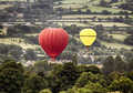 Two hot air baloons drifting ballons across a rural landscape Royalty Free Stock Photography