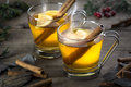 Two hot toddy cocktail drinks with cinnamon and lemmon whisky rum apple or brandy set on rustic wood Stock Image