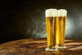 Two ice cold frothy beers in elegant long glasses Royalty Free Stock Photo