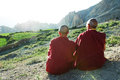 Two indian tibetan monk lama old monks in red color clothing sitting in front of mountains Stock Photo