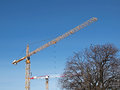 Two industrial cranes on construction site on clear blue clear sky Stock Images