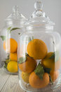 Two jars of glass filled with oranges on a wooden table Stock Photo