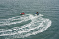 Two jet skis or personal watercraft speeding across the ocean Royalty Free Stock Photo