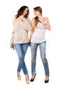 Two joyful women posing in blue jeans and high heels isolated on white Royalty Free Stock Images