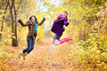 Two jumping girl in forest Royalty Free Stock Images