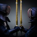 Two kendo fighters opposite each other with shinai Royalty Free Stock Images