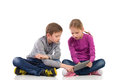 Two kid using tablet young girl and boy sitting on the floor with crossed legs and full length studio shot on white Stock Photo