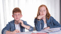 Two kids are annoyed doing their homework Royalty Free Stock Photos