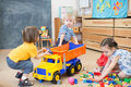 Two kids conflict or struggling for toy truck in kindergarten pull play room each to his own side Stock Photos