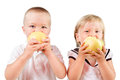 Two kids eating yellow apples isolated over white Royalty Free Stock Photo