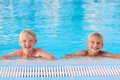 Two kids having fun in summer swimming pool happy boys laughing teenage twin brother enjoying sunny vacation playing outdoors Royalty Free Stock Images
