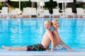 Two kids having fun in summer swimming pool happy boys laughing teenage twin brother enjoying sunny vacation playing outdoors Royalty Free Stock Photos