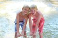 Two kids having fun in summer swimming pool happy boys laughing teenage twin brother enjoying sunny vacation playing outdoors Royalty Free Stock Photography