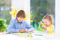 Two kids painting and cutting colorful paper butterflies happy teenager boy his cute toddler sister having fun together drawing Royalty Free Stock Photo
