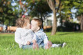 Two kids in the park little are kissing on grass Stock Photos