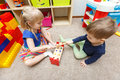 Two kids play with toy hammers and sticks in kindergarten Royalty Free Stock Photo