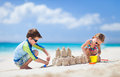 Two kids playing at beach brother and sister making sand castle tropical Royalty Free Stock Photo
