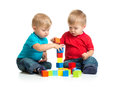 Two kids playing wooden blocks building tower