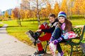 Two kids putting on roller blades children and years old couple of school boy an girl in warm autumn clothes the bench in park Stock Image