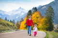 Two kids on road between snow covered mountains happy smiling boy and his little baby sister walking a and yellow autumn trees Royalty Free Stock Images
