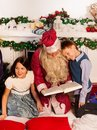 Two kids sitting with Santa reading book