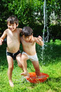 Two kids summer playing with water Stock Photo