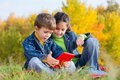 Two kids with tablet pc smiling playing and sitting on the autumn lawn Stock Photo
