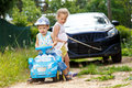 Two kids try to tow real automobile with the help of toy car Royalty Free Stock Images