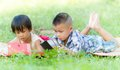 Two kids using touchscreen tablet pc on the grass Stock Images