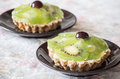 Two kiwi fruit tarts cream and with and cherries Royalty Free Stock Images