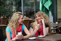 Two ladies chatting over refreshments Royalty Free Stock Image