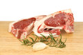 Two lamb chops raw with rosemary and garlic on a wooden board against a white background Royalty Free Stock Photo