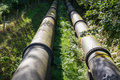 Two large black water pipes, converging in distance. Royalty Free Stock Photo