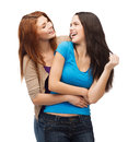 Two laughing girls looking at each other friendship and happy people concept Stock Photos