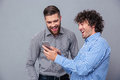 Two laughing men using smartphone Royalty Free Stock Photo
