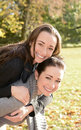 Two laughing sisters in autumn park Royalty Free Stock Photos