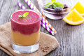 Two layered smoothie with peach and berries orange blackberries Stock Photos