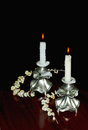 Two lighted candles in elegantnyh candlesticks still are on the table among the dead branches with gray leaves Royalty Free Stock Photography