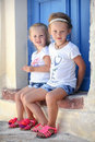 Two little adorable girls sitting on doorstep of old house in emporio village santorini greece this image has attached release Royalty Free Stock Photography