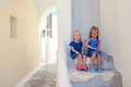 Two little adorable girls sitting on doorstep of old house in emporio village santorini greece this image has attached release Stock Photo