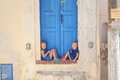 Two little adorable girls sitting on doorstep of old house in emporio village santorini greece this image has attached release Royalty Free Stock Photo