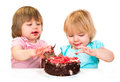 Two little baby girl eating cake Royalty Free Stock Photo