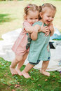 The two little baby girls playing against green grass Royalty Free Stock Photo