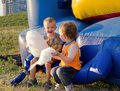 Two little boys eating candy floss laughing with enjoyment as they sit together on a plastic jumping castle at a funfair Royalty Free Stock Photo