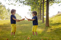 Two little boys holding swords glaring with a mad face at each other fighting outdoors in the park Royalty Free Stock Photography