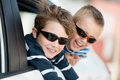 Two little boys with shades playing inside the car Royalty Free Stock Image