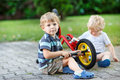 Two little boys siblings repairing bicycle outdoors Stock Photo